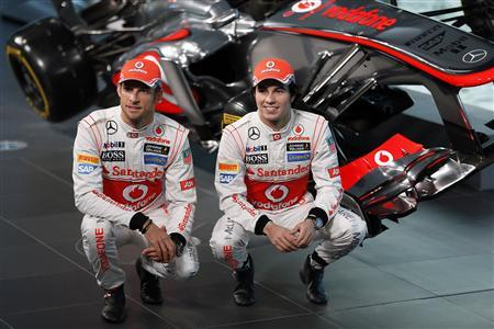 McLaren Formula One drivers Jenson Button of Britain (L) and Sergio Perez of Mexico pose for photographers after unveiling the McLaren MP4-28 car at the company's headquarters in Woking, southern England January 31, 2013. REUTERS/Stefan Wermuth