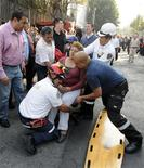 An injured woman is being transferred to a stretcher outside the headquarters of state oil giant Pemex in Mexico City January 31, 2013. An explosion rocked the Mexico City headquarters of Pemex on Thursday, killing one person, injuring more than 20 others and causing extensive damage to the building. A local emergency official said one person had died in the blast and 22 others were injured. Another four people were trapped inside the skyscraper, the official said. The blast, which media reports said was caused by machinery exploding, occurred in the basement, emergency officials said. REUTERS/Alejandro Dias