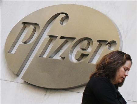 A woman walks past the Pfizer Inc. headquarters in New York, January 31, 2013. U.S. drugmaker Pfizer is expected to raise more than $2.2 billion through an initial public offering that will separate its animal health unit into a new company called Zoetis. REUTERS/Brendan McDermid (UNITED STATES - Tags: BUSINESS HEALTH)