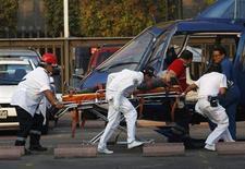 Медики везут на носилках к вертолету пострадавшего при взрыве в офисном здании в Мехико человека, 31 января 2013 года. По меньшей мере 25 человек погибли и более 100 ранены в результате взрыва, прогремевшего в штаб-квартире мексиканской государственной нефтяной компании Pemex в четверг. REUTERS/Tomas Bravo