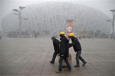 """Workers carrying boxes walk past the fog-enveloped National Stadium, also known as the """"Bird's Nest"""", at Beijing Olympic park, on a foggy day in Beijing, January 31, 2013. REUTERS/China Daily"""