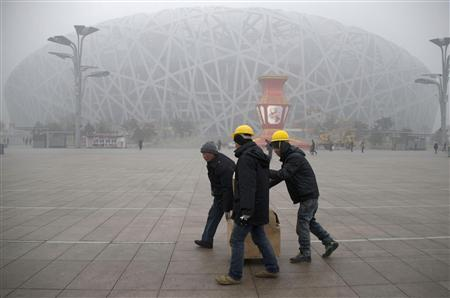 Workers carrying boxes walk past the fog-enveloped National Stadium, also known as the ''Bird's Nest'', at Beijing Olympic park, on a foggy day in Beijing, January 31, 2013. REUTERS/China Daily