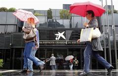 Caixabank sufrió en 2012 una fuerte caída en su beneficio neto debido a unas elevadas provisiones para sanear cartera inmobiliaria, que le llevaron a registrar un resultado inferior al esperado por los analistas. En la imagen, varias personas en la entrada de la sede de CaixaBank en Barcelona el 26 de octubre de 2012. REUTERS/Albert Gea