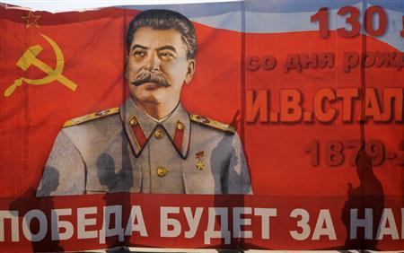 People cast shadows on a poster with a portrait of the Soviet dictator Josef Stalin during a May Day rally on International Workers' Day, or Labour Day in front of the statue of Soviet state founder Vladimir Lenin in Russia's southern city of Volgograd, in this May 1, 2011 file photo. REUTERS/Sergey Karpov/Files