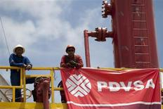 Workers stand in front of a drilling rig at an oil well operated by Venezuela's state oil company PDVSA in Morichal July 28, 2011. REUTERS/Carlos Garcia Rawlins