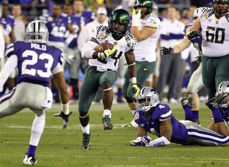 Oregon Ducks running back Kenjon Barner (24) runs past Kansas State Wildcats linebacker Arthur Brown (4) during the Fiesta Bowl football game in Glendale, Arizona, January 3, 2013. REUTERS/Darryl Webb