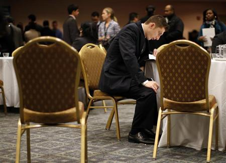 A job seeker fills out forms at a table while attending a career fair with prospective employers in New York City, October 24, 2012. REUTERS/Mike Segar