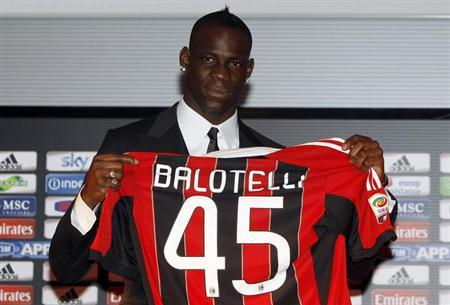 Italy's Mario Balotelli, newly signed player for AC Milan soccer club, poses for a photo with his jersey before a news conference at the San Siro stadium in Milan February 1, 2013. REUTERS/Alessandro Garofalo