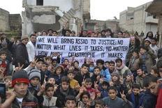 """El líder de la oposición siria se reunió el sábado con el ministro de Relaciones Exteriores de Rusia y dijo que también conversará con el canciller iraní, lo que podría abrir una ventana a un posible avance en los esfuerzos por mediar un fin a la guerra civil en Siria. En la imagen, manifestantes portan una gran pancarta (""""Llevaremos a Asad ante la justicia: no importa las vidas que cueste, no importa la catástrofe que suponga"""")durante una protesta contra el presidente sirio Bashar el Asad, tras las oraciones del viernes en Kafranbel, cerca de Idlib, el 1 de febrero de 2013 en esta foto suministrada por Shaam News Network. REUTERS/Raed Al-Fares/Shaam News Network"""