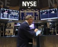 Трейдер проходит мимо информационного табло на бирже в Нью-Йорке, 18 декабря 2012 года. Американские акции выросли в пятницу до пятилетних максимумов, а Dow Jones поднялся выше 14.000 пунктов впервые с октября 2007 года, благодаря отчетам о рынке занятости и производстве. REUTERS/Brendan McDermid