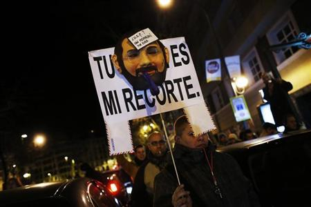 A demonstrator carries a sign with a mask resembling Spanish Prime Minister Mariano Rajoy, as they cut off traffic after a protest outside the headquarters of the ruling People's Party (Partido Popular) in Madrid February 2, 2013. REUTERS/Susana Vera