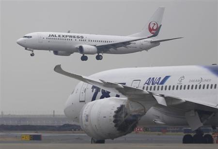 A Japan Airlines aircraft (above) approaches for landing as an All Nippon Airways' Boeing Co's 787 Dreamliner plane parks on the tarmac at Haneda Airport in Tokyo February 4, 2013. REUTERS/Toru Hanai/Files