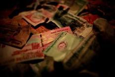 Купюры различных азиатских валют в Сингапуре 17 января 2013 года. Европейская полиция выявила сотни футбольных матчей по всему миру, как клубных, так и на уровне сборных, которые могли быть договорными, принеся в общей сложности 8 миллионов евро прибыли. REUTERS/Thomas White