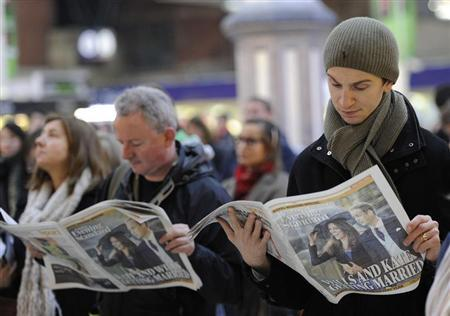 Commuters read copies of the Evening Standard newspaper, featuring a front page headline about the engagement of Britain's Prince William to Kate Middleton, at Victoria rail station in London, November 16, 2010. REUTERS/Paul Hackett