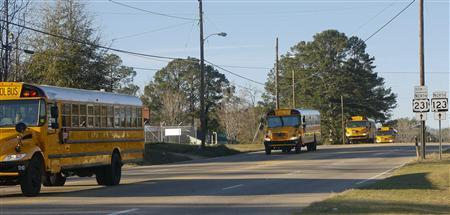 A line of school buses in the procession to the gravesite after the funeral for bus driver Charles Albert Poland Jr. at Ozark Civic Center, near Midland City, Alabama, February 3, 2013. REUTERS/Phil Sears (UNITED STATES - Tags: CRIME OBITUARY)