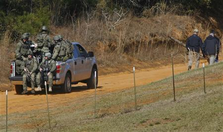 Law enforcement officials including the FBI are driven onto the scene of a shooting and hostage taking near Midland City, Alabama February 1, 2013. REUTERS/Phil Sears (UNITED STATES - Tags: CRIME LAW)
