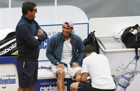 Spanish tennis player Rafael Nadal is assisted with his knee bandage as he talks to his uncle and coach Toni Nadal (L) before a training session at country club Las Salinas in Vina del Mar City, about 121 km (75 miles) northwest of northwest of Santiago, February 4, 2013. REUTERS/Eliseo Fernandez