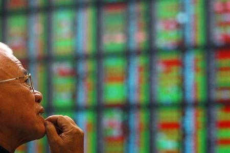 A man looks at stock market prices inside a brokerage in Taipei October 7, 2010. REUTERS/Nicky Loh/Files