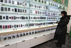 Женщина смотрит на витрину с сотовыми телефонами в салоне Мегафона в Санкт-Петербурге 15 ноября 2012 года. Темпы роста сектора услуг РФ в январе снизились третий месяц подряд и были минимальными с сентября 2012 года, свидетельствует исследование компании Markit, проведенное для HSBC. REUTERS/Alexander Demianchuk