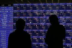 Due persone guardano gli indici di borsa su un display a Tokyo. REUTERS/Kim Kyung-Hoon