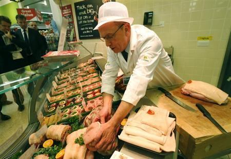 Morrisons supermarket butcher Roy Craven prepares meat at a store in London November 21, 2012. BREUTERS/Luke MacGregor