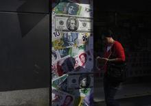 Человек проходит мимо пункта обмена валюты в Гонконге 24 октября 2012 года. Пара евро/доллар отскочила от недельного минимума и уже превысила уровни открытия глобальной сессии вторника после часа европейской торговли благодаря спросу на подешевевшую единую валюту. REUTERS/Bobby Yip