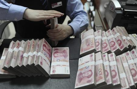 An employee counts 100 Chinese yuan banknotes at a bank in Hefei, Anhui province, January 21, 2013. REUTERS/Stringer