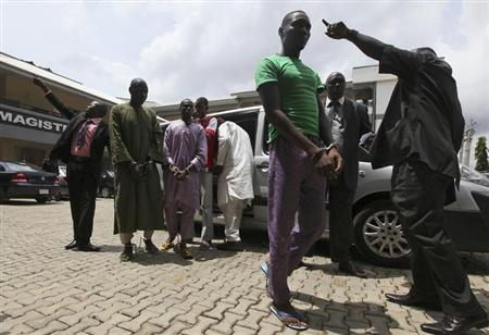 A man, suspected of being involved in a series of bomb attacks, walks handcuffed outside the Wuse magistrate court in Nigeria's capital Abuja in this file photo taken September 13, 2011. REUTERS/Afolabi Sotunde