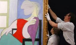 """Sotheby's employees straighten """"Femme assise pres d'une fenetre"""" from 1932 by Pablo Picasso at Sotheby's in London January 31, 2013. REUTERS/Suzanne Plunkett"""