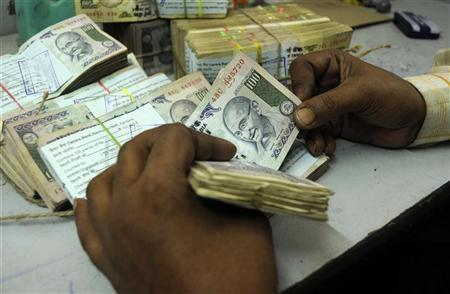 An employee counts currency notes at a cash counter inside a bank in Agartala, January 29, 2010. REUTERS/Jayanta Dey/Files
