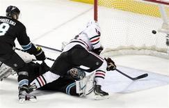 """Центрфорвард """"Чикаго"""" Маркус Крюгер забрасывает шайбу в ворота вратаря """"Сан-Хосе"""" Антти Ниеми во втором периоде матча регулярного чемпионата НХЛ 10 февраля 2012 года. """"Чикаго"""" отыграл во вторник две шайбы в матче регулярного чемпионата Национальной хоккейной лиги против """"Сан-Хосе"""" и добился в гостях волевой победы, позволившей ему остаться лидером НХЛ по числу набранных очков. REUTERS/Beck Diefenbach"""