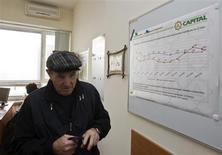 """Клиент в офисе частного пенсионного фонда """"Капитал"""" в Алма-Ате 24 января 2013 года. Правительство Казахстана, решившее объединить частные пенсионные фонды с активами на $21 миллиард, создаст собственный фонд к июлю и передаст его в управление Нацбанку, сообщил вице-премьер. REUTERS/Shamil Zhumatov"""