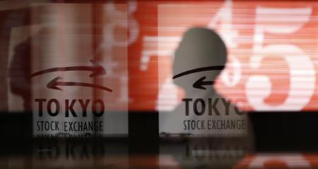 Men walk past logos at the Tokyo Stock Exchange in Tokyo February 6, 2013. REUTERS/Toru Hanai/Files