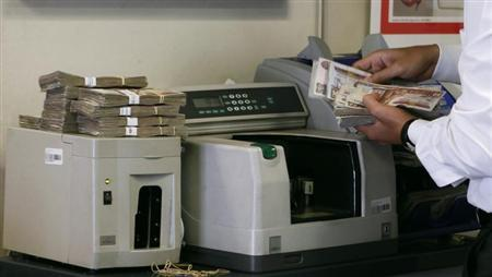 An employee counts money in a bank in Cairo, August 27, 2012. REUTERS/Asmaa Waguih