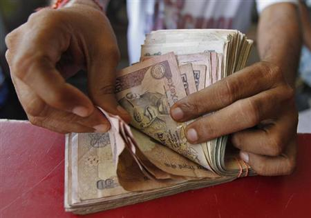 A grocery shop owner counts rupees notes in Ahmedabad May 23, 2012. REUTERS/Amit Dave