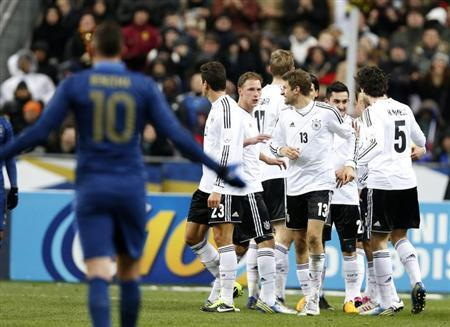 Germany's Thomas Muller (13) celebrates with team mates after scoring as France's Karim Benzema (L) reacts during their international friendly soccer match at the Stade de France stadium in Saint-Denis, near Paris, February 6, 2013. REUTERS/Charles Platiau