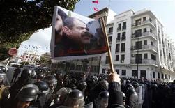 Los islamistas en el poder en Túnez disolvieron el Gobierno el miércoles y prometieron celebrar elecciones lo más pronto posible en un intento por calmar las mayores protestas desde la revolución de hace dos años, que estallaron por la muerte de un líder opositor. En la imagen, manifestantes tunecinos corean eslóganes durante una manifestación tras la muerte del líder opositor Chokri Belaid (cuya foto aparece en la bandera), a las afueras del ministerio del Interior en Túnez, el 6 de febrero de 2013. REUTERS/Anis Mili