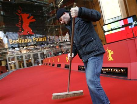 A worker cleans the red carpet for the upcoming 63rd Berlinale film festival in front of the main festival cinema in Berlin February 6, 2013. REUTERS/Fabrizio Bensch