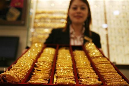 A shop assistant displays gold bangles for the camera at a jewellery store in Singapore March 4, 2008. REUTERS/Vivek Prakash/Files