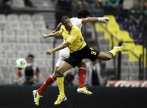 Duel entre le Jamaïcain Ryan Johnson (au premier plan) et le Mexicain Javier Rodriguez, au Stade Azteca, à Mexico. Le Mexique a mal entamé la phase qualificative pour la Coupe du monde de football 2014 dans la zone Concacaf en concédant le nul (0-0). /Photo prise le 6 février 2013/REUTERS/Henry Romero