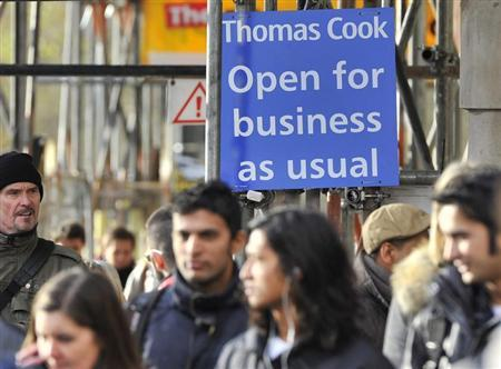 Pedestrian walk near a sign outside a branch of Thomas Cook in London December 14, 2011. REUTERS/Toby Melville
