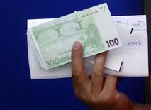 Мужчина держит купюру в 100 евро, полученную из банкомата в Афинах, 13 июня 2012 года. Евро растет после успешного аукциона госдолга Испании и благодаря покупкам азиатскими инвесторами. REUTERS/Yannis Behrakis