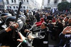 Протестующие в Тунисе вступают в стычку с полицией у стен МВД 6 февраля 2013 года. Исламистская правящая коалиция отправила правительство Туниса в отставку и пообещала скорые выборы, пытаясь восстановить спокойствие после того, как убийство лидера оппозиции привело к самым крупным за последние два года акциям протеста по всей стране. REUTERS/Anis Mili