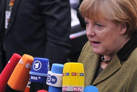 Germany's Chancellor Angela Merkel talks to the media as she arrives at the EU council headquarters for an European Union leaders summit meeting to discuss the European Union's long-term budget in Brussels February 7, 2013