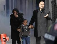 Cidadãos tunisianos fogem de gás lacrimogênio lançado pela polícia durante uma manifestação na cidade de Tunis. A polícia lançou gás lacrimogêneo para dispersar centenas de jovens que protestavam na cidade de Gafsa, no sul do país, contra o assassinato do líder da oposição Chokri Belaid na quarta-feira, informaram testemunhas à Reuters. 07/02/2013 REUTERS/Louafi Larbi
