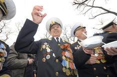 Un monumento ruso a la botella de vodka ha sido derribado por temor a que pueda considerarse publicidad ilegal al trago preferido del país. En esta imagen de archivo, veteranos de la Segunda Guerra Mundial beben vodka y comen en la celebración del Día de la Victoria en el puerto oriental ruso de Vladivostok, el 9 de mayo de 2012. REUTERS/Yuri Maltsev