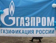 Баннер с логотипом Газпрома на церемонии, посвященной окончанию проведения газопровода в аул Али-Кую в Ставропольском крае, 14 ноября 2012 года. Газпром сократит дивидендные выплаты за 2012 год по сравнению с уровнем 2011 года, но уровень вознаграждения акционеров за 2013 год может вырасти, сообщил Газпром в презентации для аналитиков. REUTERS/Eduard Korniyenko