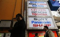 Men walk past logos of Japan's electronics firms at the Akihabara electronics store district in Tokyo February 7, 2013. REUTERS/Toru Hanai