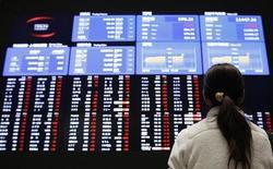 Женщина смотрит на экраны с котировками на Токийской фондовой бирже 6 февраля 2013 года. Азиатские фондовые рынки, кроме Японии, выросли в пятницу за счет высоких внешнеторговых показателей Китая. REUTERS/Toru Hanai