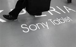 Las acciones de Sony cayeron más de un 10 por ciento a 1.365 yenes el viernes en Tokio después de que sus ganancias en el trimestre octubre-diciembre no alcanzaron las expectativas del mercado, elevando el escepticismo sobre que el fabricante de televisores Bravia y la PlayStation pueda recuperar su liderazgo. En la imagen, un hombre pasa sobre una publicidad de Sony en Tokio el 6 de febrero de 2013. REUTERS/Shohei Miyano